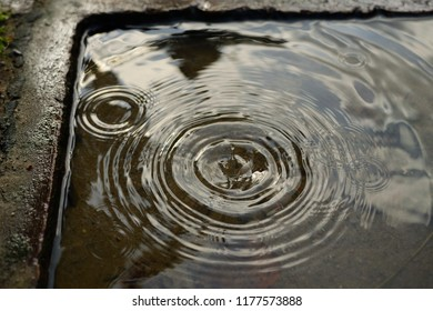 Raindrops in a puddle, on a water pump