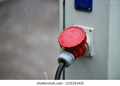 Raindrops are seen on industrial electric plug during heavy rain