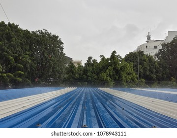 Rainfall falling on blue white polyvinyl chloride roof on grey sky and trees background.