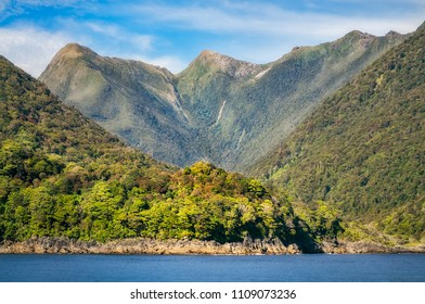 Rainforest and mountain range at Doubtful Sound on a adventure cruise, a location so remote that can only be reached by water across Lake Manapouri. Fiordland National Park, New Zealand, South Island.