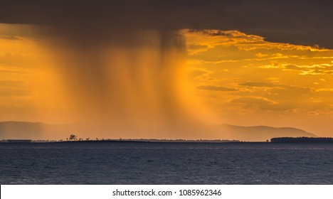 raining during sunset in the lake with golden sky