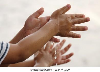 Raining into children's hands.