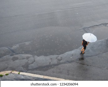 Raining. Man with white umbrella goes in the heavy rain. Falling raindrops. Top view. Bad weather. Possible flood. Natural disaster. Wet street. Puddle. Municipal storm sewer system and water utility