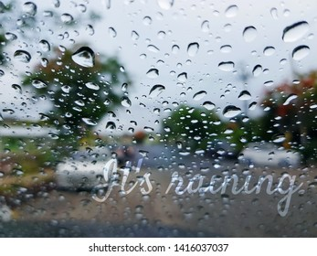 It's Raining Texts Overlay on Blurred Background of Rain Droplets on Mirror.