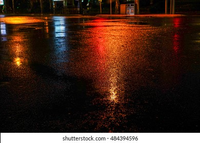 Rainstorm in the big city night, light from the shop windows reflected on the road on which cars travel. View from the level of asphalt