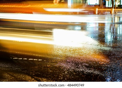 Rainstorm in the big city night, light from the shop windows reflected on the road on which cars travel. View from the level of asphalt.