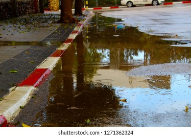 Rainwater floods the road and the pavement. Flooding, winter rain, winter weather in Israel