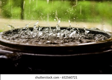Rainwater harvesting during Monsoon season in Kerala. Side view of water being collected in huge black polymer tank, splashing drops of water. Water day.