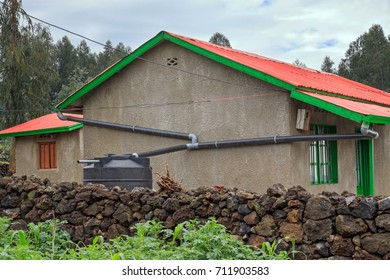 Rainwater harvesting from roof in Rwanda. Roof gutters under a roof with corrugated sheets collect rainwater which is stored in a 1500 liter container next to the house.