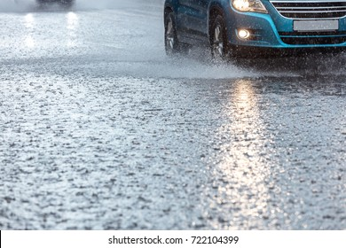 rainwater spraying from car wheels. city road during heavy rain.