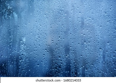 Rainy background, rain water drops on the window or in shower stall, autumn season backdrop, abstract textured wallpaper.