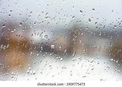 Rainy city background. Raindrops on window glass. Wet home window with raindrops.