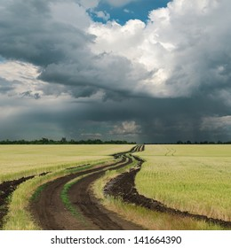 rainy clouds over field with road