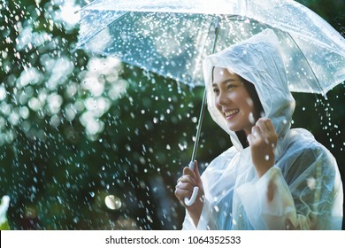 Rainy day asian woman wearing a raincoat outdoors. She is happy.
