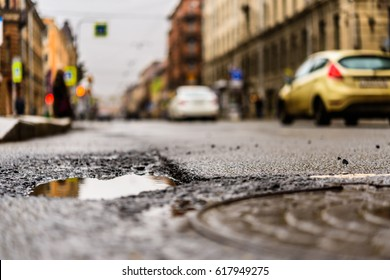 Rainy day in the big city, the cars drive along the old road. Close up view of a hatch at the level of the asphalt