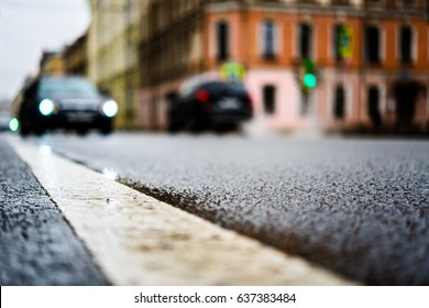 Rainy day in the big city, the cars are driving down the street. Close up view from the level of the dividing line