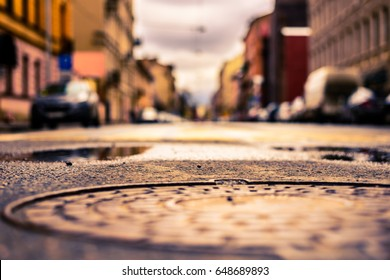 Rainy day in the big city, the parked cars on an empty road. Close up view of a hatch at the level of the asphalt, image in the yellow-blue toning