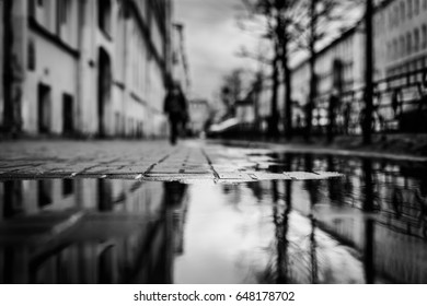 Rainy day in the big city, the sidewalk with pedestrians. Close up view from the level of the puddle on the sidewalk, image in the black and white tones