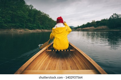 Rainy day boat ride. Rear view of woman in yellow raincoat paddling canoe. Active, adventure, outdoors, canoeing, kayaking