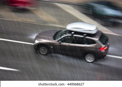 Rainy day in the city: A driving car, with a storage box on the roof, in the street hit by the heavy rain with hail, in motion blur