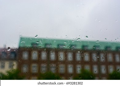 Rainy day in Copenhagen, Denmark. Old building behind the window with rain drops