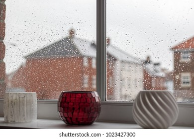 Rainy day depression. Selective focus on raindrops on modern house window glass pane. Bleak view ahead of a modern housing estate through a wet double-glazed window pane covered with rain drops.