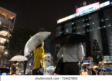 Rainy day in Ebisu: couple waiting at a crossing, carrying umbrellas.