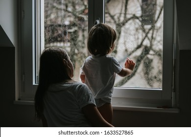 Rainy day. Little toddler boy with his sister looking outside through  wet window from his room missing mother.  Siblings love, care and support. Lifestyle. Quarantine and isolation period at home