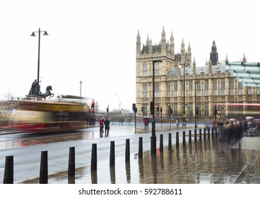rainy day in London city, people and car traffic. Westminster in background. United Kingdom
