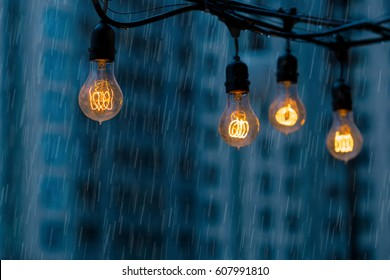 Rainy day at the modern city street. Light bulbs garland against urban buildings background.