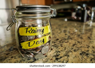"Rainy Day Money Jar. A clear glass jar filed with coins and bills, saving money. The words ""Rainy Day"" written on the outside."