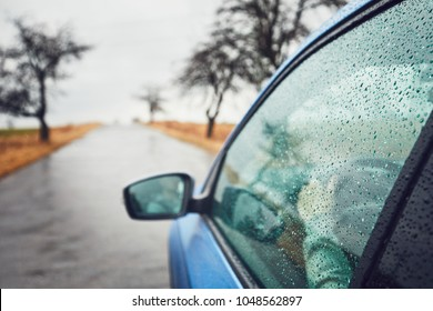 Rainy day on the road. Man is driving car in rain. Selective focus on raindrops.