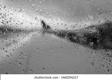Rainy day out jet window on runway in black & white.