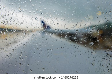 Rainy day out jet window on runway.