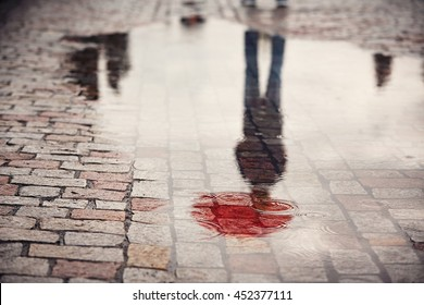 Rainy day. Reflection of young man with red umbrella in puddle on the city street during rain.