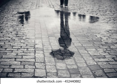 Rainy day. Reflection of young man with umbrella in puddle on the city street during rain.