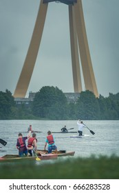 Rainy day in Riga city. People boating in river Daugava between the islands. TV tower and bridge in the background. Outdoor activities in bad weather