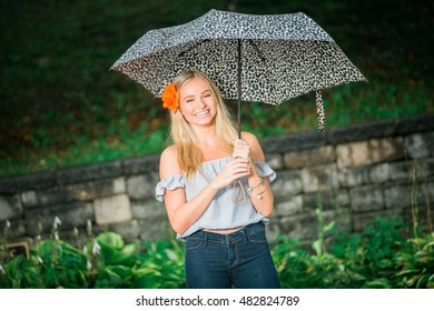 Rainy day. Teen girl poses with umbrella for a high school senior portrait photo outdoors