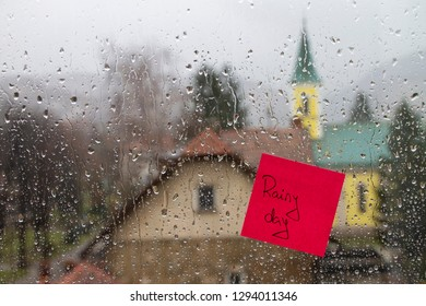 Rainy day text on window glass