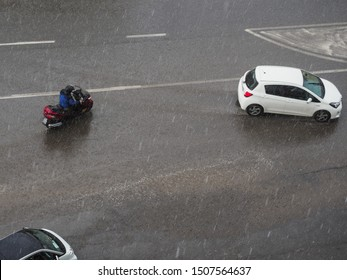 Rainy day and water droplets. Traffic in city during heavy rain. Wet street, puddles on the road can cause traffic problems. Motorcycle and car moving chaotic. Blurred background due to water splashes