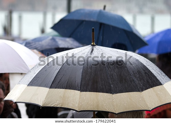 Rainy day and wet umbrellas in crowded street