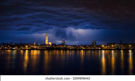 Rainy night in Antwerp. Nice light reflection on the river Scheldt. Antwerp, the city of diamonds, with one of the biggest harbors in Europe. Rainy clouds above the cathedral of our Lady.