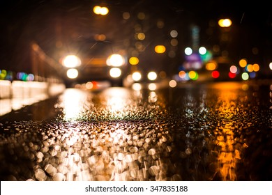 Rainy night in the big city, approaching headlights of car traveling along the avenue. View from the level of the curb on the road