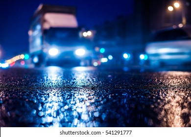 Rainy night in the big city, the approaching truck headlights shine through the mist. Close up view from the asphalt level, image in the blue tones