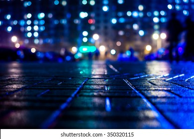 Rainy night in the big city, blinding lights from the front of the house. View from the sidewalk level paved with bricks, in blue tones