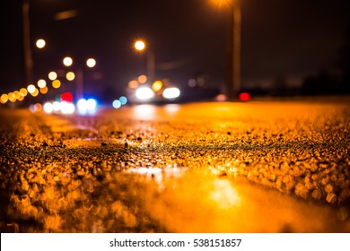 Rainy night in the big city, the blinding headlights of the approaching cars. Close up view from the level of the dividing line - Shutterstock ID 538151857