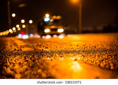 Rainy night in the big city, the blinding headlights of the approaching bus. Close up view from the level of the dividing line - Shutterstock ID 538151971