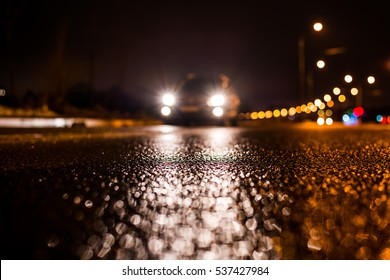 Rainy night in the big city, the car traveling towards the headlights illuminate the road. Close up view from the asphalt level