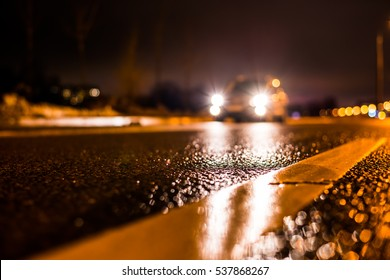 Rainy night in the big city, the car traveling on the highway and shines a blinding light. Close up view from the level of the dividing line