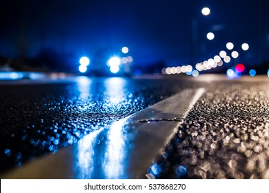 Rainy night in the big city, the car traveling on the highway and shines a blinding light. Close up view from the level of the dividing line, image in the blue tones